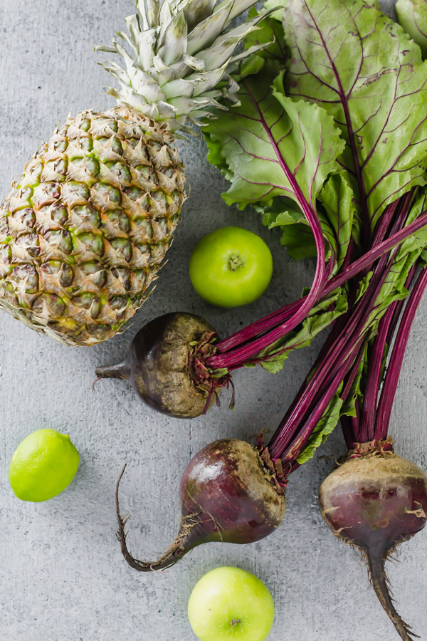 a pineapple, apple, and beets laying in a table