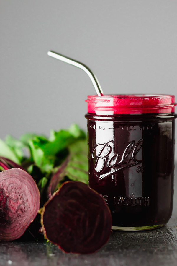 A cup with beet juice and beets on the table