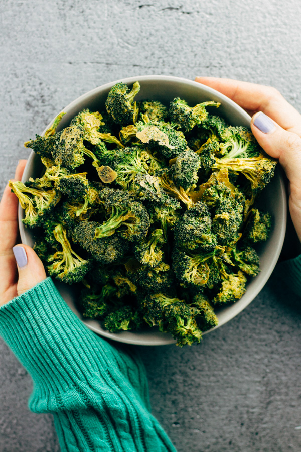 A bowl filled with dehydrated raw vegan cheezy broccoli chips