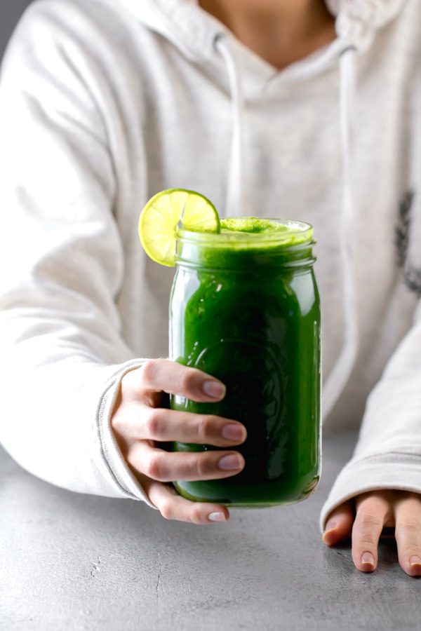 A woman holding a mason jar with green juice