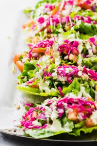 raw vegan romaine lettuce tacos lined up on a dish