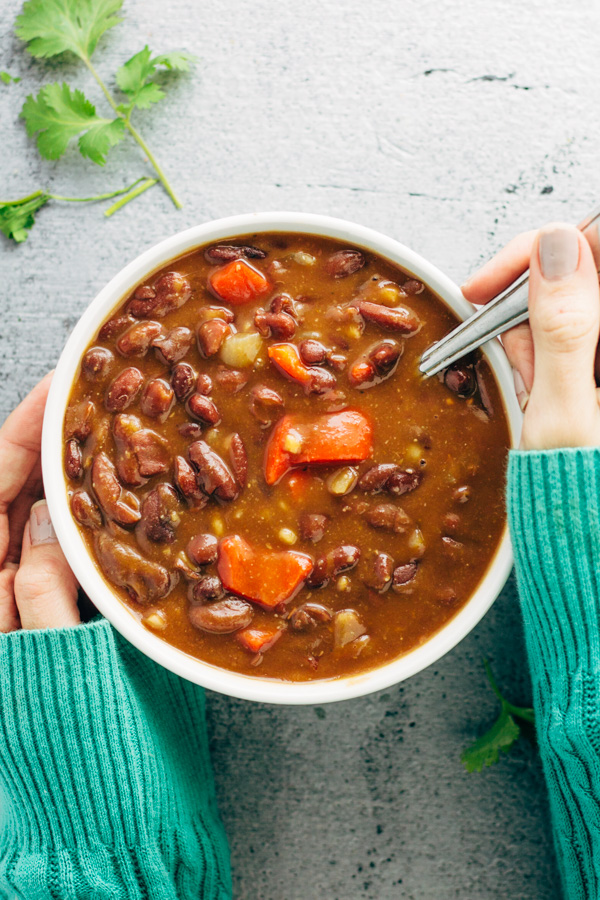 A bowl of vegan red kidney bean soup with two hands and a spoon