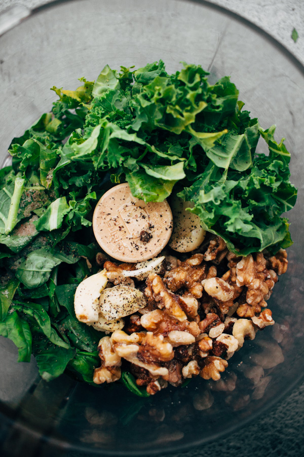 a food processor with kale, basil, walnuts, and other pesto ingredients