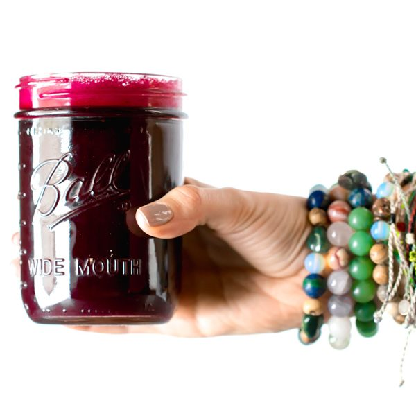 a hand holding a cup of beet juice