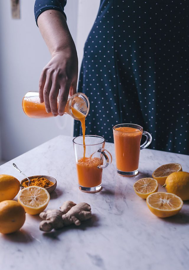 Woman pouring orange juice into a cup
