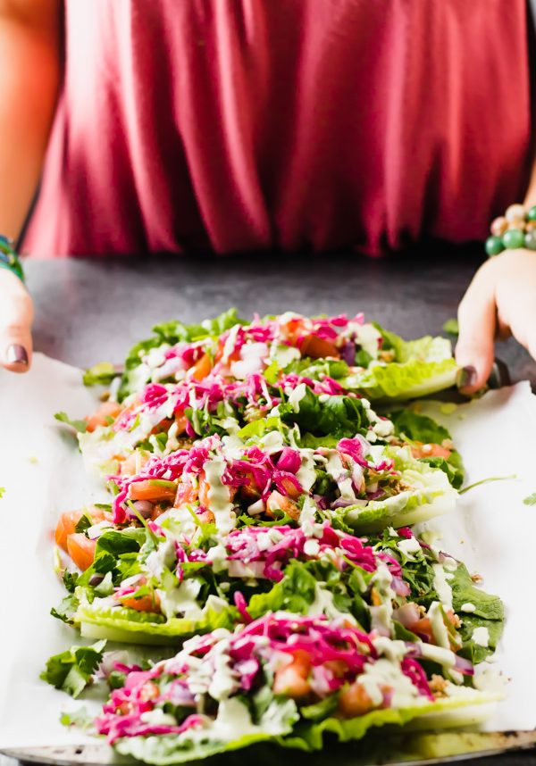 A baking dish with raw vegan romaine lettuce tacos