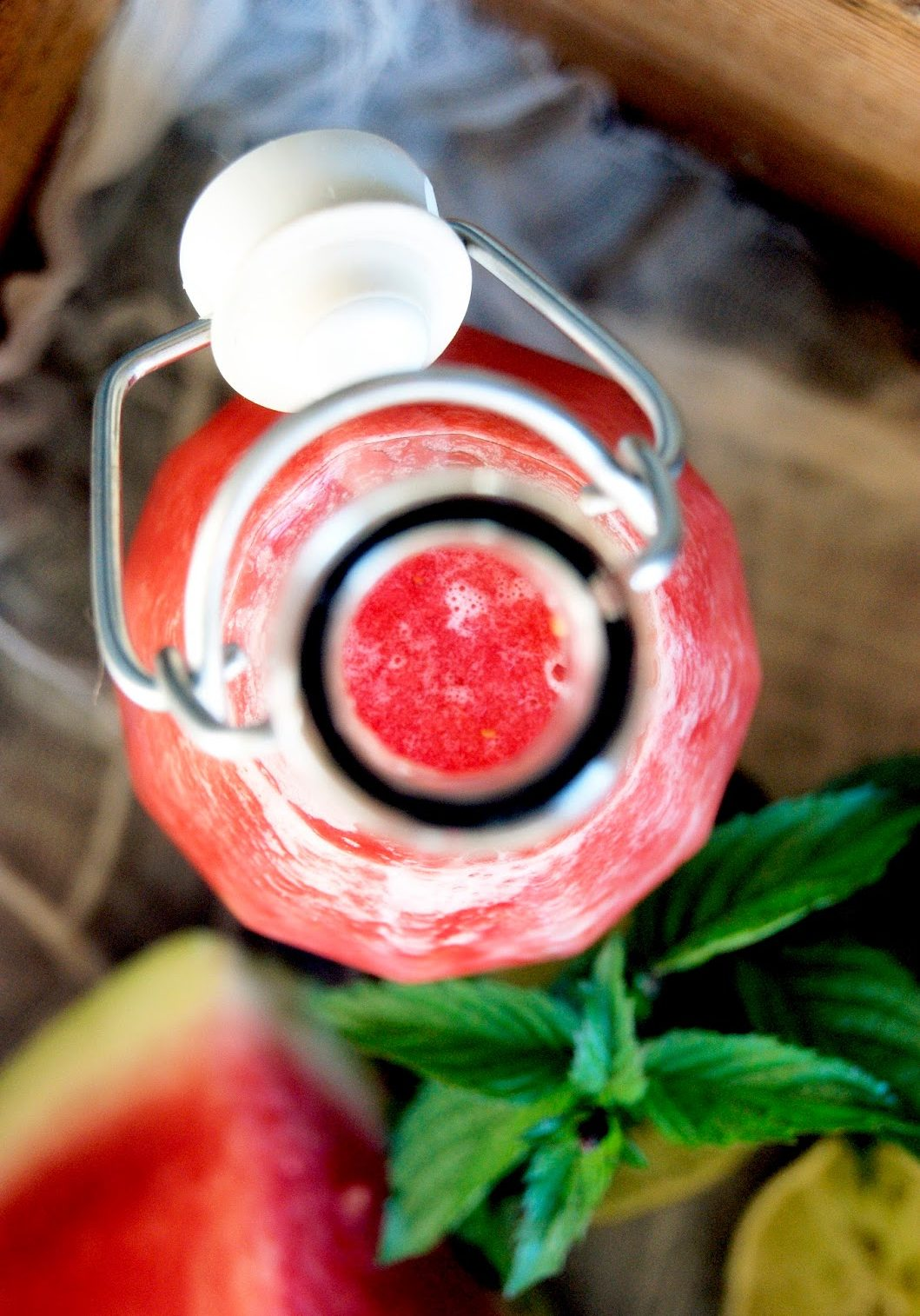 A top down view of a glass bottle with watermelon juice inside