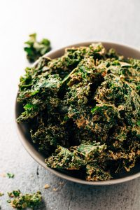 a bowl with dehydrated raw vegan spicy kale chips