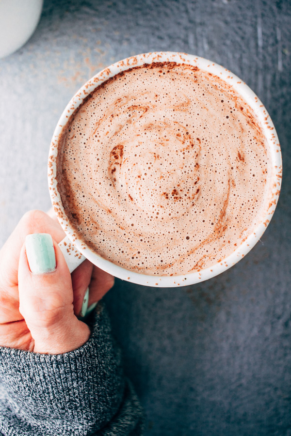 A hand holding a cup of vegan blender hot chocolate