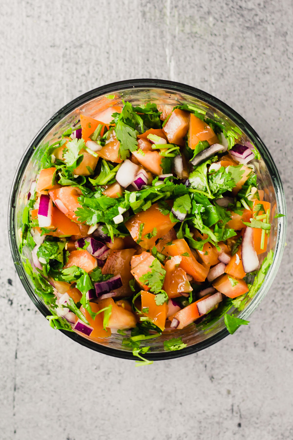 a glass dish on a table with easy homemade pico de gallo