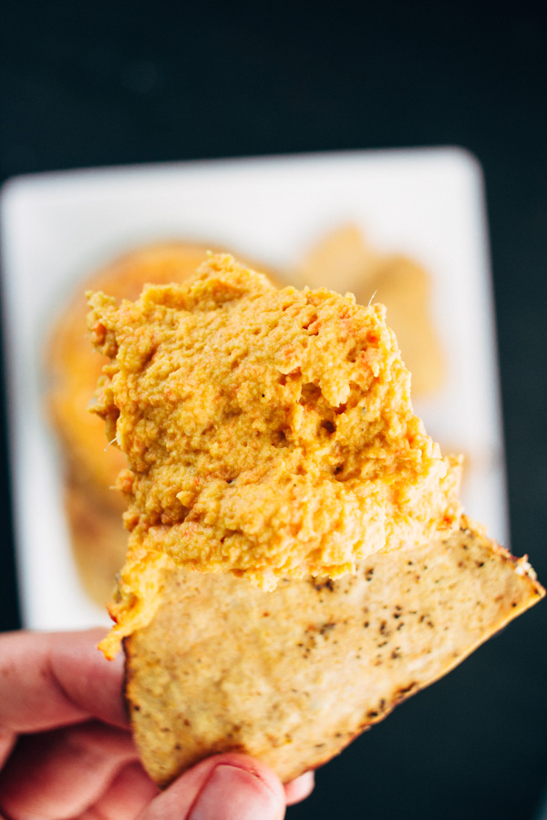 a tortilla chip with vegan roasted carrot and garlic hummus