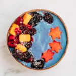 blue spirulina smoothie in a bowl topped with fruits