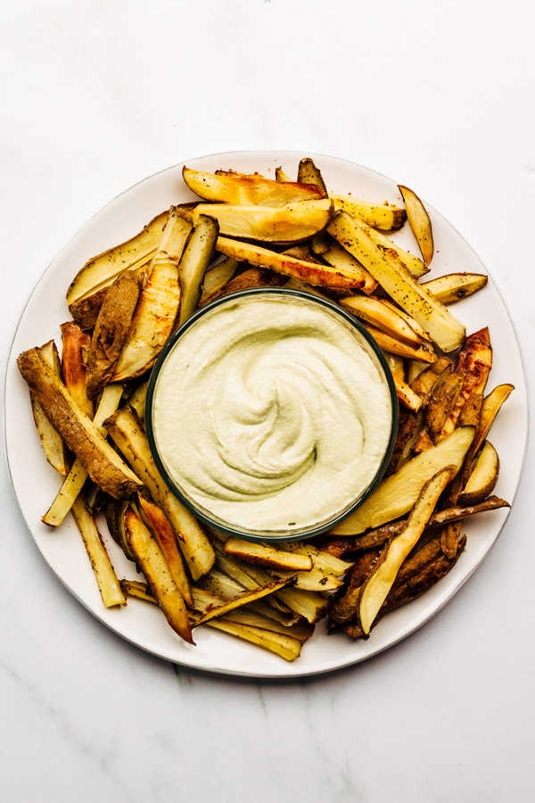 a plate with oven baked fries oil free with avocado tahini vegan dip sauce