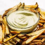 Oven baked vegan fries with avocado tahini sauce served on a plate
