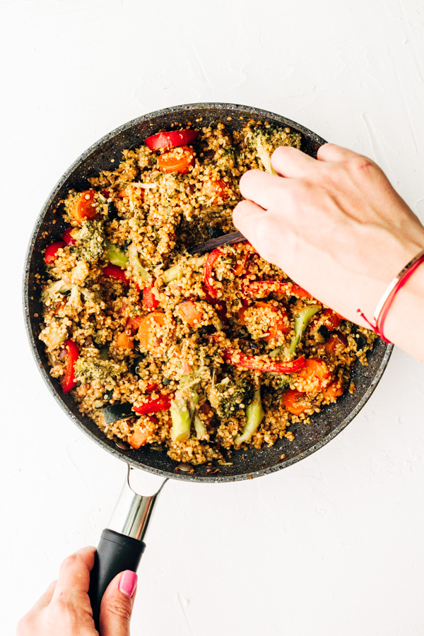 a pan holding vegan quinoa fried rice with a hand mixing the quinoa around.