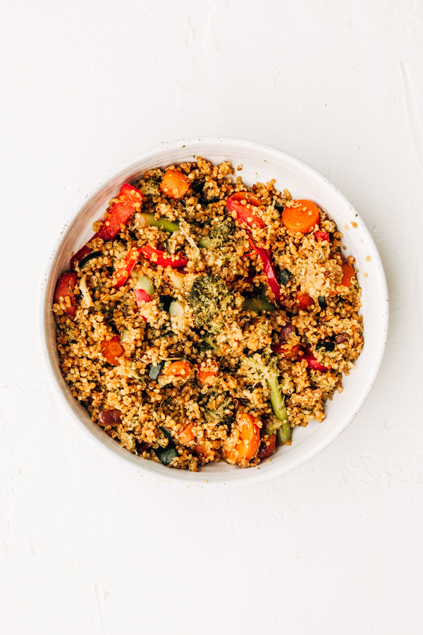 a white bowl with vegan quinoa fried rice served inside of it.