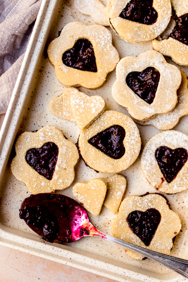 A tray with vegan linzer cookies and a spoon