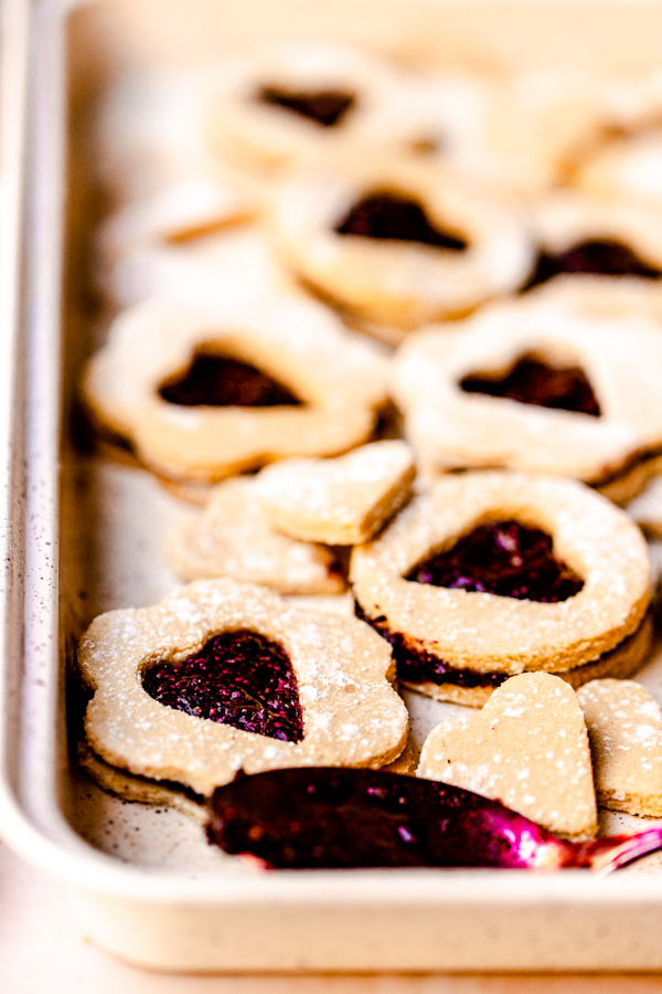 A baking sheet with vegan linzer cookies on them with a spoon