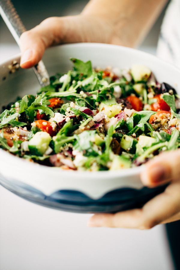 A woman holding a bowl that is loaded with healthy greek salad