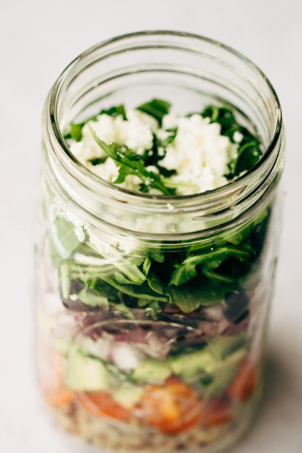 A large mason jar with easy greek salad loaded inside the jar