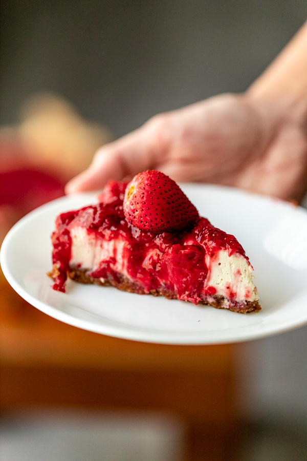 A strawberry cheesecake on a white plate