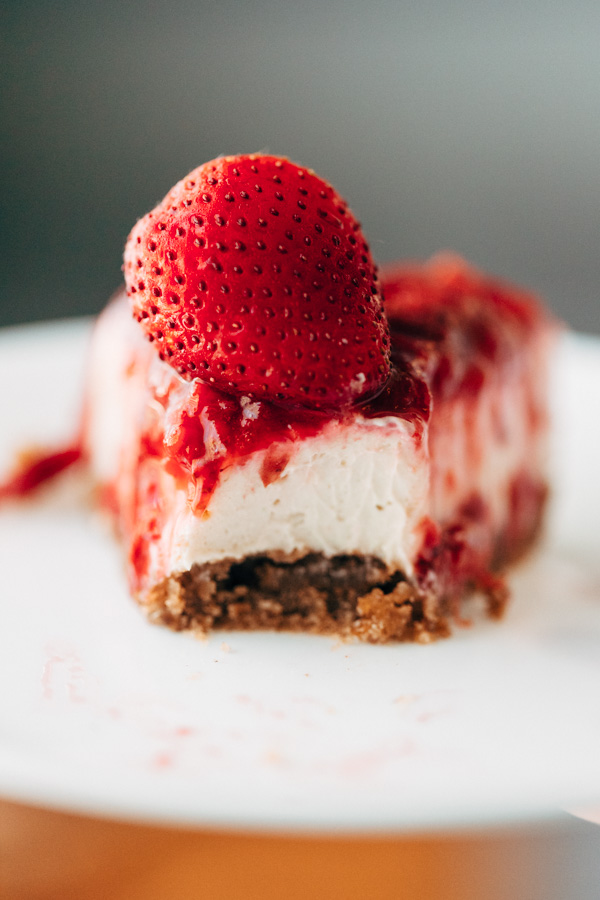 A close up shot of a no bake strawberry cheesecake with a bite taken out of it