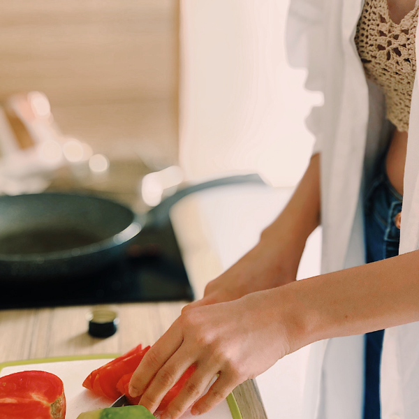 a women cutting vegetables in a kitchen