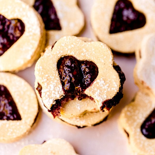 A pile of valentine's day themed vegan linzer cookies with a bite in it.