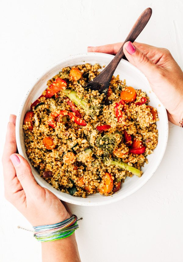 a bowl of quinoa fried rice with hands holding the bowl