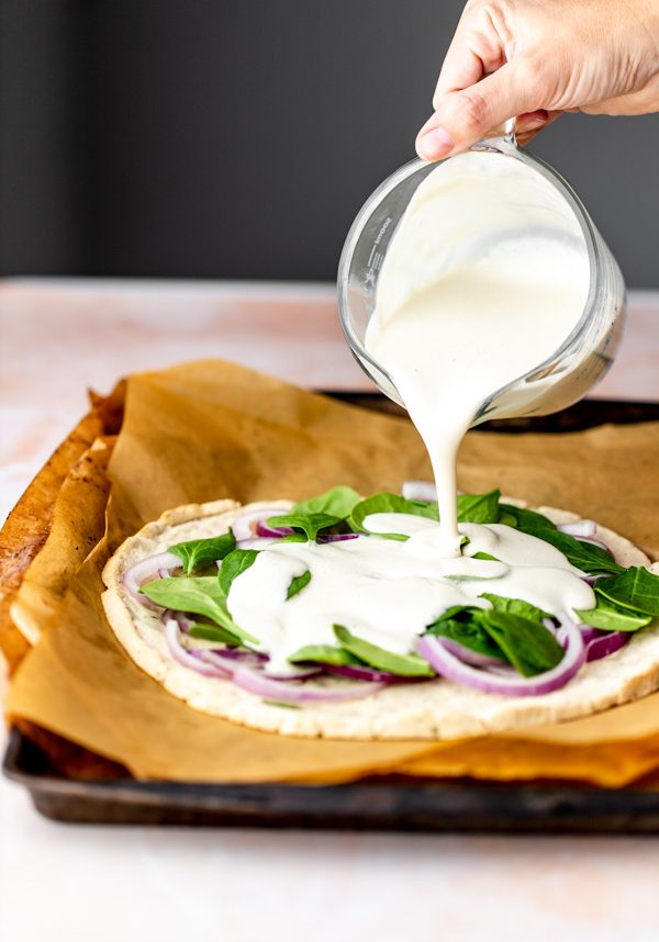 vegan white cashew cheese sauce being poured on top of a homemade pizza